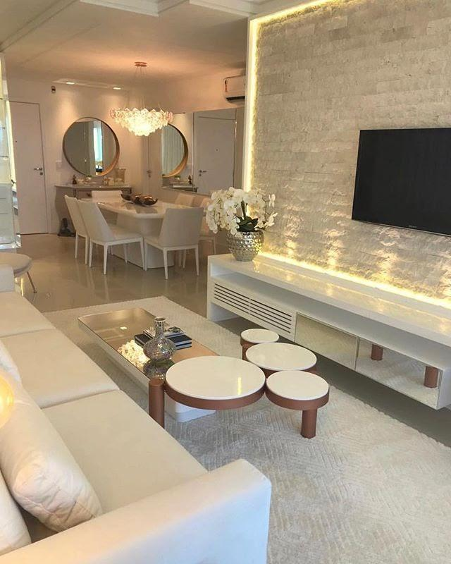 Flat living room with sofa, carpet, flat screen television and coffee table in the living room. In addition to dining table, chairs, mirror and chandelier.