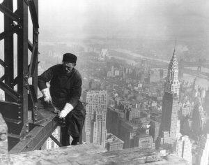 Workers building the Empire State Building, with the Chrysler Building in the background